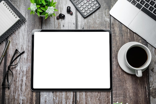 Vista superior do tablet da mesa de madeira com uma tela branca em branco e dispositivos de trabalho. brincar.