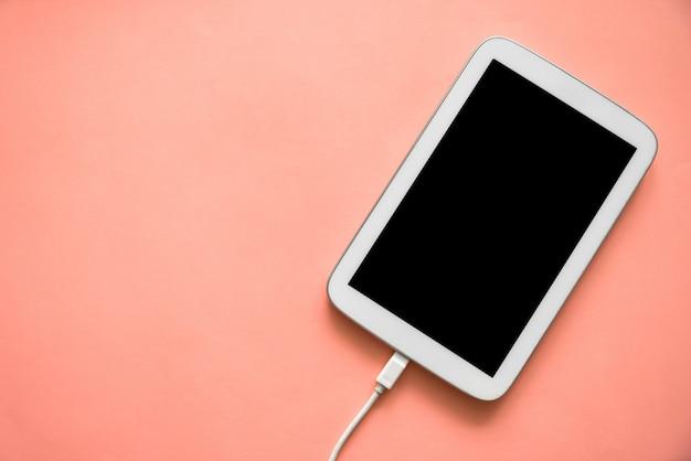 Vista superior do tablet de cor branca com tela preta e cabo carregado