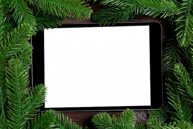 Vista superior do tablet decorado com uma moldura feita de abeto em fundo de madeira. conceito de tempo de ano novo