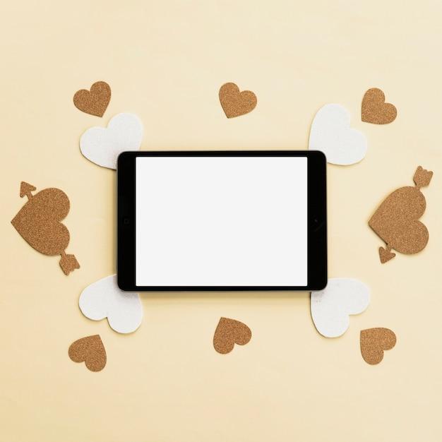 Vista superior do tablet digital com adesivo de coração branco e dourado na superfície bege