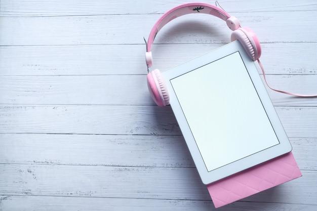 Vista superior do tablet digital com tela branca e fone de ouvido na mesa
