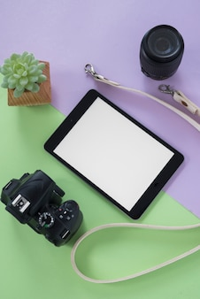 Vista superior do tablet digital com tela em branco; câmera; lentes da câmera; cinto e planta suculenta sobre fundo duplo