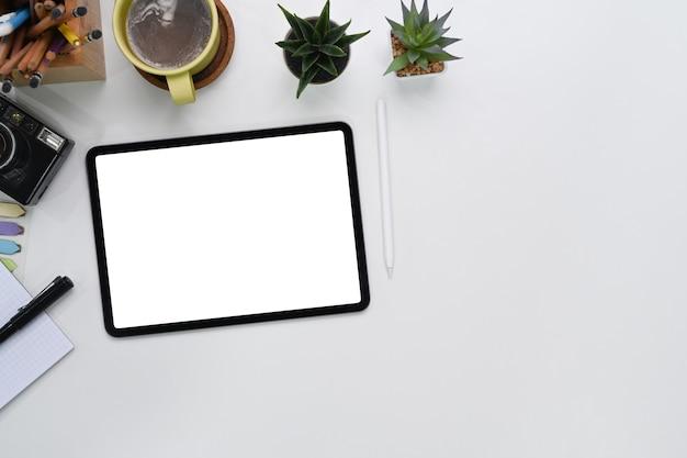 Vista superior do tablet digital de maquete com tela vazia, câmera, xícara de café, caderno e espaço de cópia no espaço de trabalho do fotógrafo.