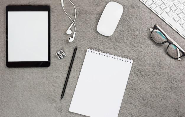 Vista superior do tablet digital em branco; fone de ouvido; rato; teclado e óculos com bloco de notas em espiral