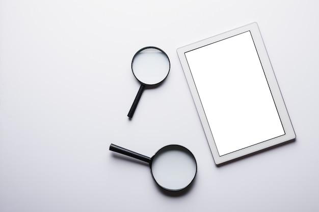 Vista superior do tablet, duas lupas em um fundo branco