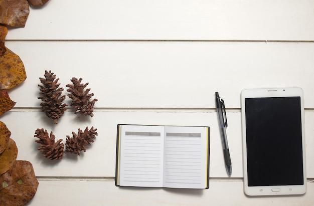 Vista superior do tablet e do caderno com caneta no fundo branco da mesa, design plano leigo