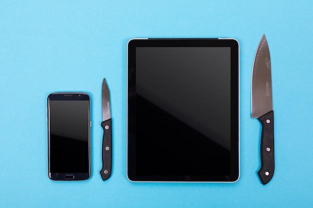 Vista superior do tablet e utensílios de cozinha ao lado isolado em um fundo azul