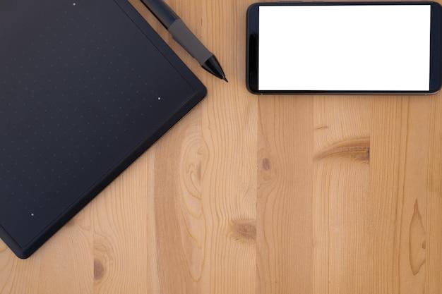Vista superior do tablet gráfico e smartphone em madeira