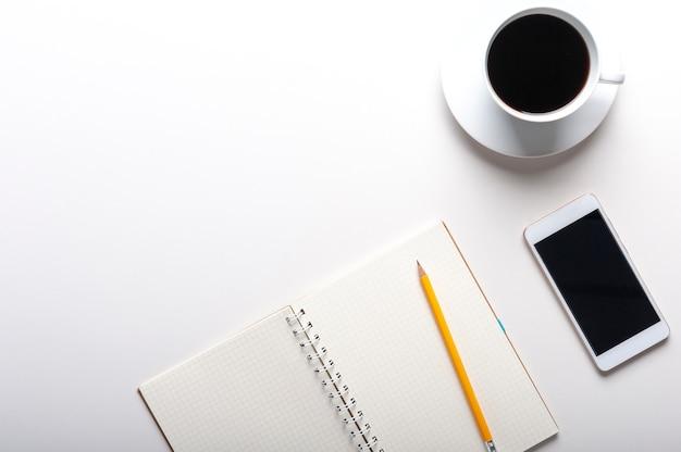 Vista superior do tablet, smartphone, calculadora, notebook e uma xícara de café sobre fundo branco