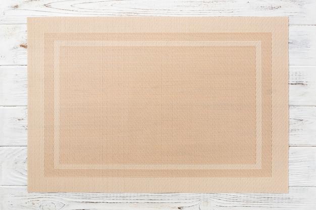 Vista superior do tapete marrom têxtil para jantar em fundo de madeira com espaço de cópia