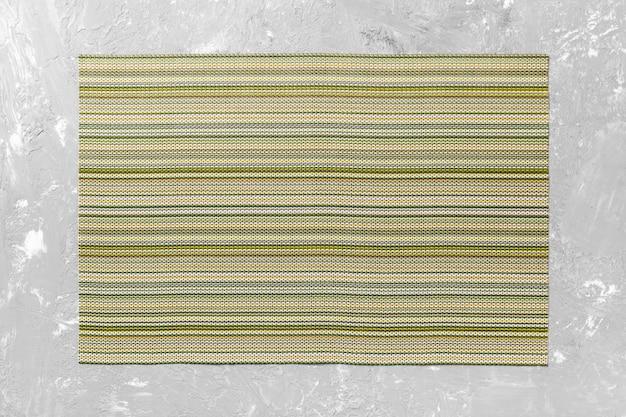 Vista superior do tapete têxtil verde para jantar no cimento