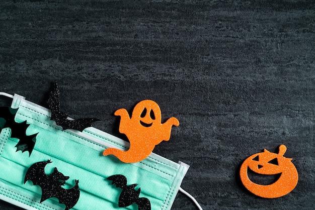 Vista superior do tecido não tecido da decoração do conceito de halloween em fundo de ardósia preto escuro com máscara.