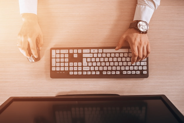 Vista superior do teclado com as mãos dos homens. espaço de cópia de monitor preto grátis para o projeto. brilho quente da luz do sol