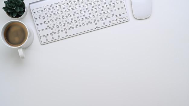 Vista superior do teclado de sagacidade de mesa de escritório branco, xícara de café e espaço de cópia.