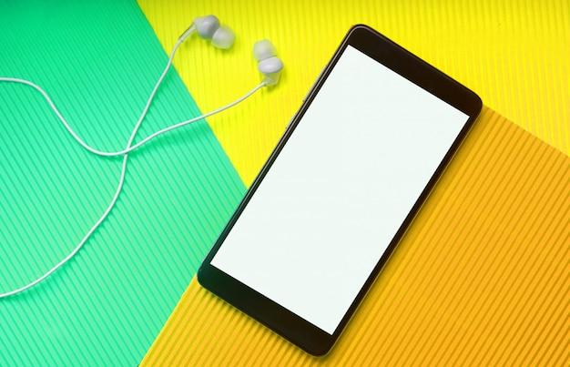 Vista superior do telefone celular com fones de ouvido na moda neo menta multicolor vibrante