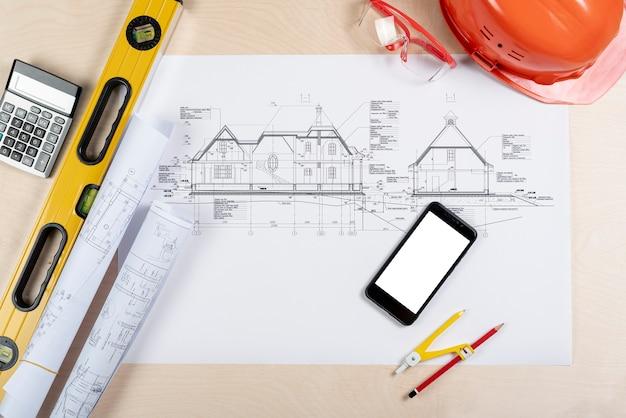Vista superior do telefone em cima da maquete de planos arquitetônicos