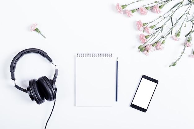Vista superior do telefone inteligente, fones de ouvido, caderno de papel, lápis e flores deite na mesa branca