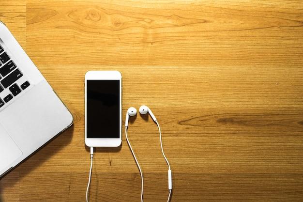 Vista superior do telefone inteligente, laptop e fone de ouvido na mesa de madeira - copysapce