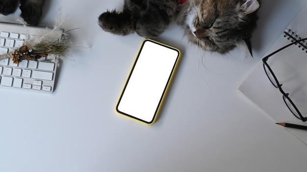 Vista superior do telefone móvel com tela branca e gato na mesa branca no local de trabalho casual.
