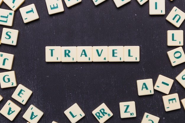 Vista superior do texto de viagem com letras scrabble sobre pano de fundo preto