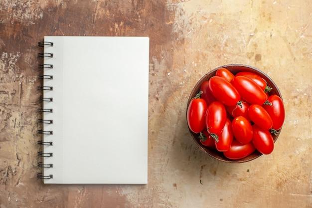 Vista superior do tomate cereja em uma tigela de madeira, um caderno em fundo âmbar