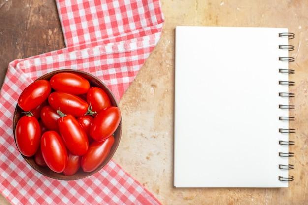 Vista superior do tomate cereja em uma tigela de madeira, uma toalha de cozinha, um caderno em fundo âmbar