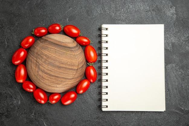Vista superior do tomate cereja em volta de uma placa de madeira e um caderno em solo escuro