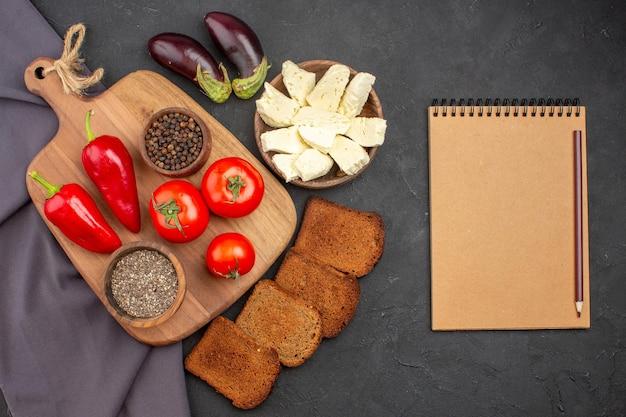 Vista superior do tomate fresco com escuro. pães e queijo branco no preto