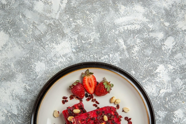 Vista superior do torrão vermelho fatiado com nozes e morangos vermelhos frescos na mesa branca