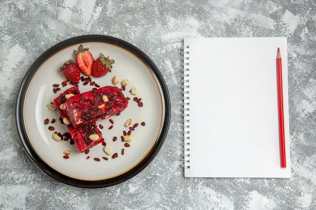 Vista superior do torrão vermelho fatiado com nozes e morangos vermelhos frescos na superfície branca clara