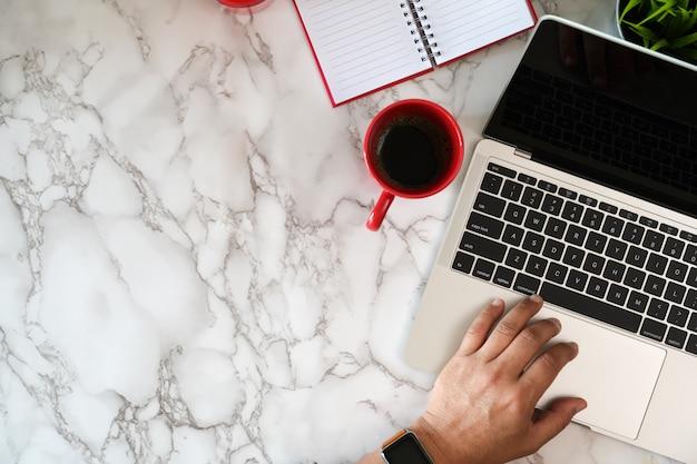 Vista superior do trabalhador masculino digitando no laptop na mesa de mármore