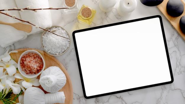 Vista superior do tratamento de spa e conceito de relaxamento com tablet de tela em branco, sal de spa, pedras quentes e outros acessórios de spa