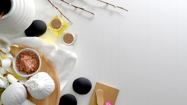 Vista superior do tratamento de spa e conceito de relaxamento com toalha branca, sal de spa, pedras quentes e outros acessórios de spa