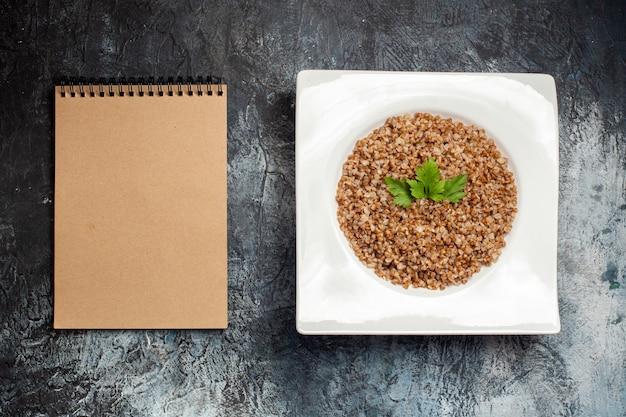 Vista superior do trigo mourisco cozido dentro do prato com o bloco de notas no fundo cinza.