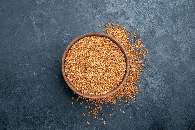 Vista superior do trigo sarraceno cru dentro da placa marrom no espaço cinza