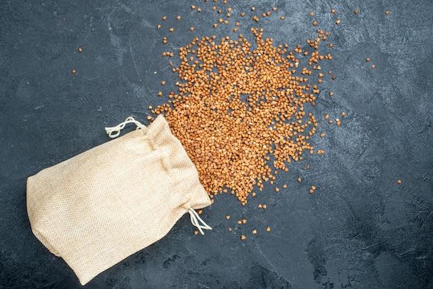 Vista superior do trigo sarraceno cru dentro e fora do saco no espaço cinza
