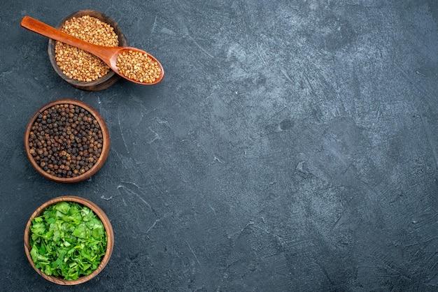 Vista superior do trigo sarraceno e verduras com pimenta no espaço escuro