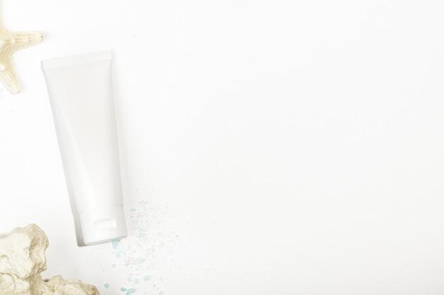 Vista superior do tubo branco com estrela do mar, pedras e sal marinho. estilo de maquete, copie o espaço no lado direito. recipiente em branco para produtos cosméticos naturais. skincare e conceito de cosmetologia orgânica.