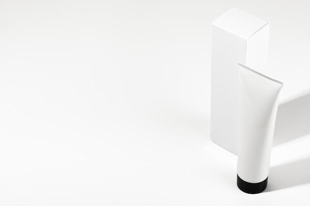 Vista superior do tubo branco sem marca com tampa preta e caixa de embalagem. frasco em branco para creme, protetor solar ou loção hidratante em fundo de sombra clara. conceito de produtos cosméticos. estilo de maquete.