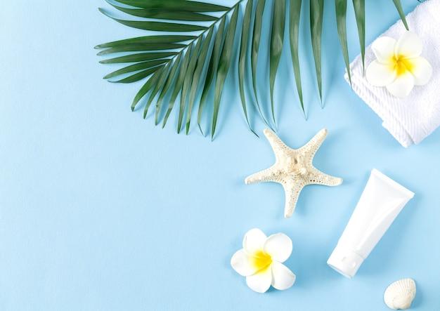 Vista superior do tubo cosmético de plástico branco em branco, folha de palmeira, toalha e conchas do mar no fundo azul do verão