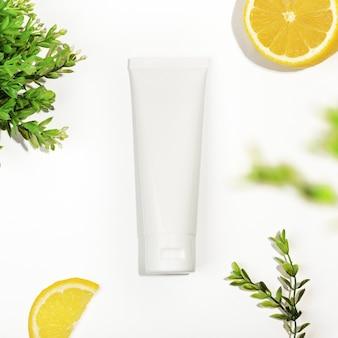 Vista superior do tubo de plástico branco com limão e planta verde. tubo sem marca para creme, esfoliante, loção ou soro. estilo de maquete, copie o espaço. skincare, produtos cosméticos naturais e orgânicos.