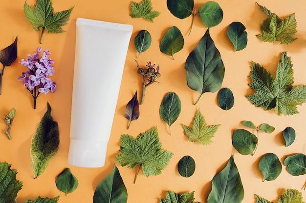 Vista superior do tubo de plástico branco e folhas verdes das árvores na mesa de laranja.
