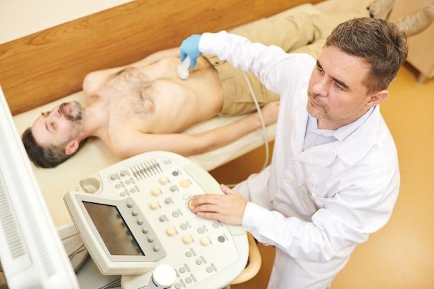 Vista superior do ultrassonografista concentrado em jaleco usando a sonda transdutora na barriga do paciente durante o procedimento de ultrassom
