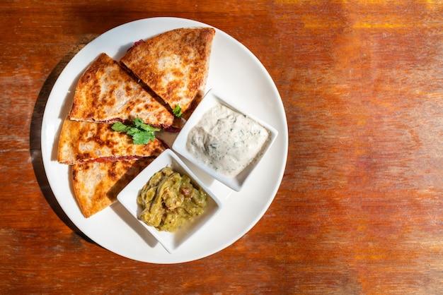 Vista superior do vegan quesadilla: tortilla de trigo integral grelhada recheada com batata doce e feijão vermelho, queijo quesso vegan servido com molho de guacamole e molho tzaziki.