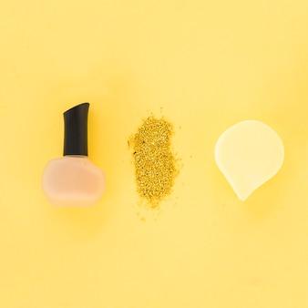 Vista superior do verniz das unhas; glitter e esponja dispostas em uma linha em fundo amarelo