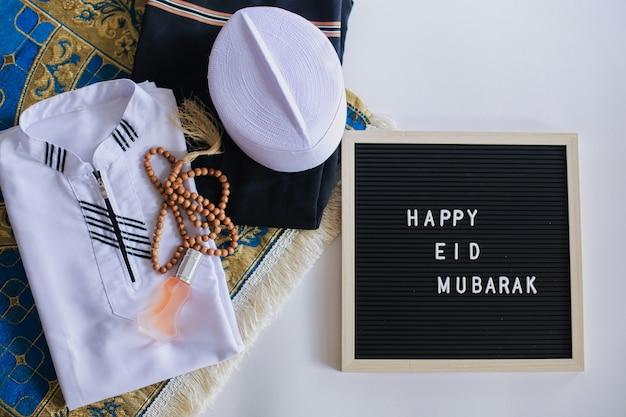 Vista superior do vestido tradicional muçulmano e contas de oração no tapete de oração com quadro de avisos: happy eid mubarak