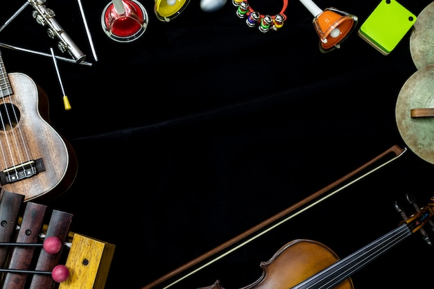 Vista superior do violino e ukulele com instrumentos de percussão no fundo preto