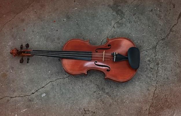 Vista superior do violino no piso térreo de cimento da superfície do grunge, mostra detalhes do instrumento acústico