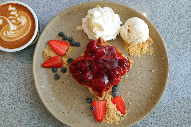 Vista superior do waffle com molho de morango, frutas, sorvete de baunilha e café cappuccino