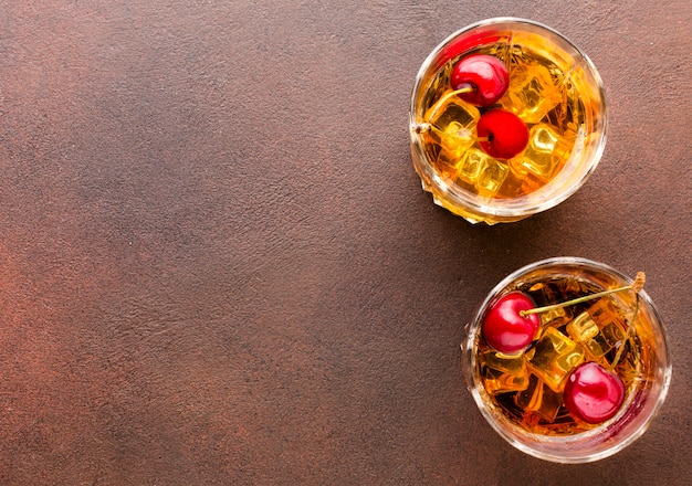 Vista superior do whisky com gelo com cerejas e cópia-espaço